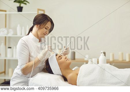 Beautician Makes A Young Beautiful Girl A Vacuum Facial Treatment For Rejuvenation.