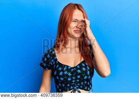 Young beautiful redhead woman wearing casual clothes over blue background smelling something stinky and disgusting, intolerable smell, holding breath with fingers on nose. bad smell