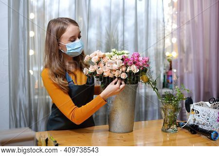 Florist Woman In A Medical Mask For Protection From Coronavirus. Pandemic Concept, Working During An