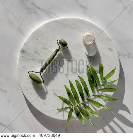 Jade Face Roller And Cream For Facial Massage Therapy. Flat Lay On Round Marble Podium On Matching S