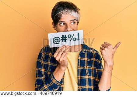 Young hispanic man covering mouth with insult message paper pointing thumb up to the side smiling happy with open mouth