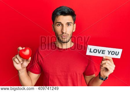 Young handsome man holding red heart and love you message relaxed with serious expression on face. simple and natural looking at the camera.