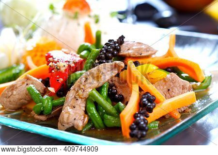 Stir Fried, Oriental Dish With Pork Meat, Green Beans, Carrots, Red Pepper, Served On A Glass Plate.