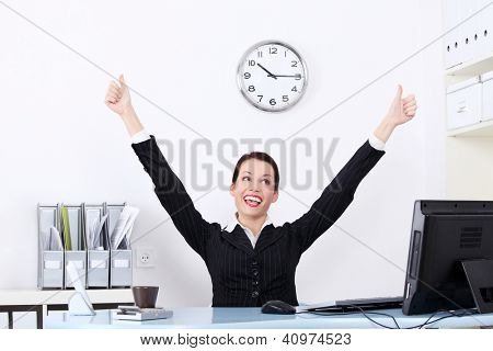 Successful attractive businesswoman with hands up at the desk in her office.