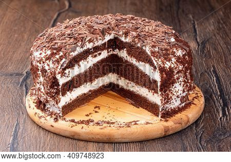 Creamy Chocolate Cake Sprinkled With Chocolate Chips With A Cut. Layer Cake On A Wooden Cutting Boar