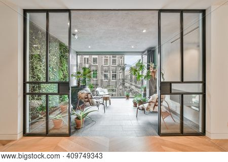 Elegant Room With A Balcony With Various Plants And Beautiful Chairs