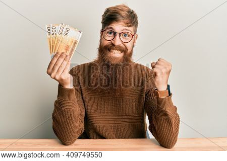 Young irish redhead man holding 500 norwegian krone banknotes sitting on the table screaming proud, celebrating victory and success very excited with raised arm