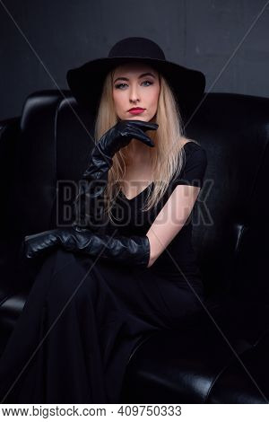 Sexy Long-haired Blonde With Bright Makeup In A Black Hat And A Stylish Elegant Evening Dress Is Sit