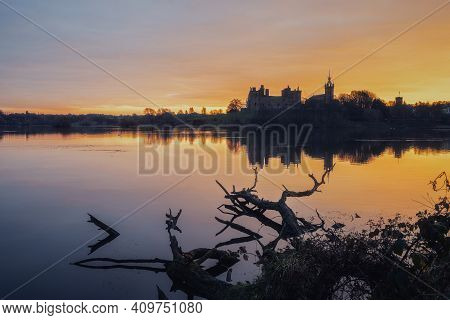 Old Scottish Castle On The Lake At Sunrise. Trees In The Water In The Foreground. Linlithgow Palace,