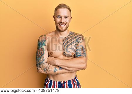 Young caucasian man wearing swimwear shirtless happy face smiling with crossed arms looking at the camera. positive person.