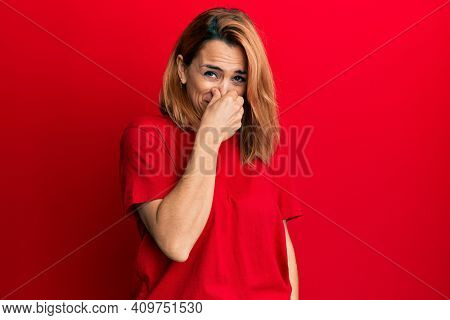 Hispanic young woman wearing casual red t shirt smelling something stinky and disgusting, intolerable smell, holding breath with fingers on nose. bad smell