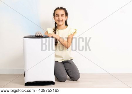 Cute Little Girl Standing Breathing At Air Purifier. Clean Air Concept