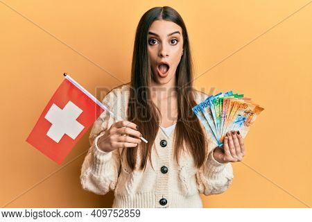 Beautiful brunette young woman holding switzerland flag and franc banknotes afraid and shocked with surprise and amazed expression, fear and excited face.