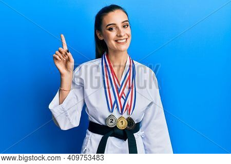 Beautiful brunette young woman wearing karate fighter uniform and medals surprised with an idea or question pointing finger with happy face, number one