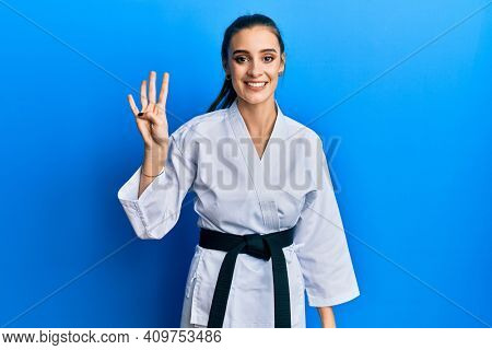 Beautiful brunette young woman wearing karate fighter uniform with black belt showing and pointing up with fingers number four while smiling confident and happy.