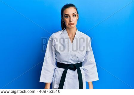 Beautiful brunette young woman wearing karate fighter uniform with black belt depressed and worry for distress, crying angry and afraid. sad expression.