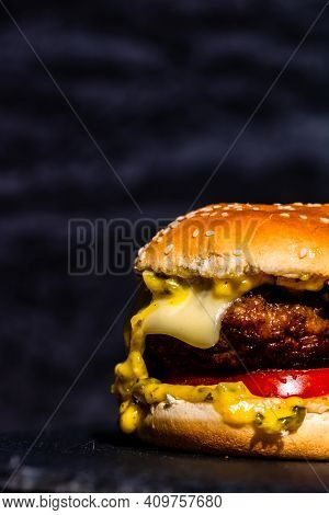 Juicy Grilled Beef Cheeseburger Isolated On Black Background. Cheeseburger With Melted Cheese On Bla