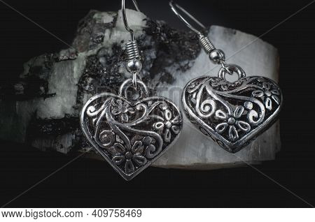 Silver Earrings In The Form Of Hearts On A Natural Stone. Jewelry Earrings Close Up