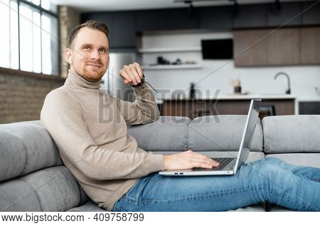 Inspired Programmer With Earphones And Laptop On The Lap, Smiling Looking Up, Sitting On A Sofa, Wor