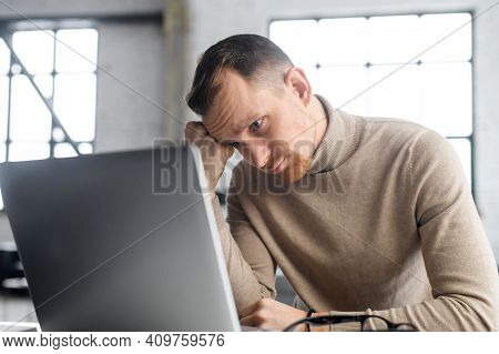 Young Disappointed Businessman Sitting At The Laptop, Propped His Head On His Fist And Watching At T