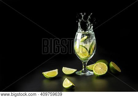 Splash Of Water In A Glass With Lime And Ice On A Black Background.