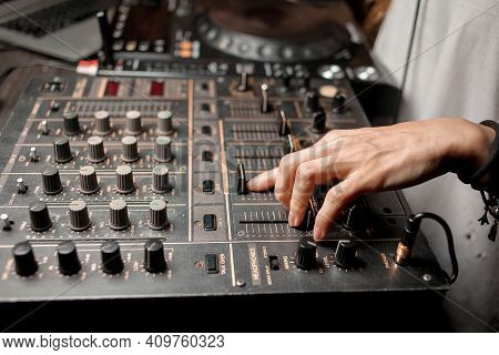 The DJ's hand on the DJ mixer. Dj on the turntables. DJ's hand on a DJ mixer close-up. Girl , Man DJ