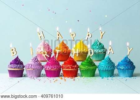 Rainbow colored cupcakes with birthday candles spelling happy birthday