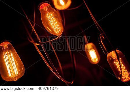 Edison Lamp On A Black Background. Incandescent Lightbulb With A Dark Background With Bokeh. Tungste