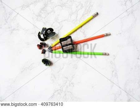 Three Graphite Pencils With Black Plastic Casing, Sharpener And Shavings. Ecology Concept Of Using N