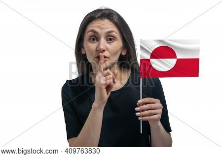 Happy Young White Woman Holding Flag Of Greenland And Holds A Finger To Her Lips Isolated On A White