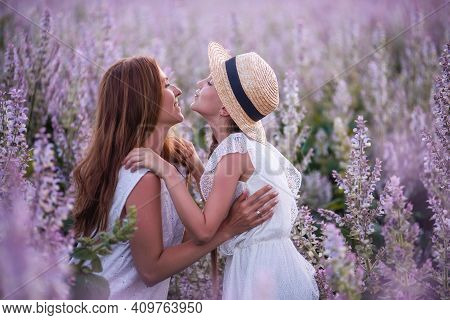 Young Mother In White Sundress Hugs Little Daughter In Straw Hat. Girl Kisses Woman Among Blooming P