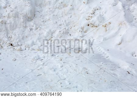 Textured Surface Of Dirty Snowdrift On Winter Day