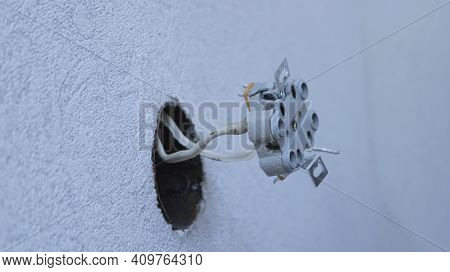 Ceramic Double Euro Socket Screwed To The Cable Under Voltage Close-up Against The Background Of The