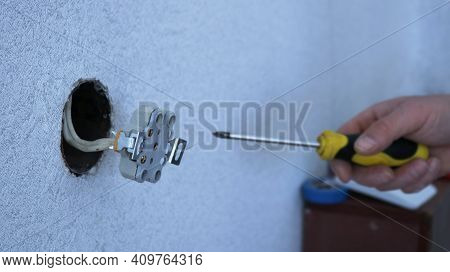 Socket Connected To White Wires In The Wall In The Process Of Fixing With A Screwdriver In The Hand