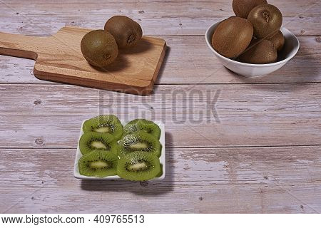 Rectangular Plate With Cut Kiwifruit. And Several Whole Kiwifruit On Board And Bowl. Wooden Base, Fr