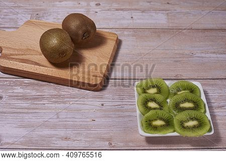 Rectangular Plate With Cut Kiwifruit And Several Whole Kiwifruit On A Board. Wooden Background, Fron