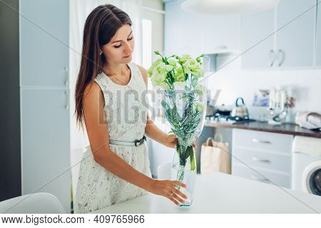 Woman Puts Bouquet Of Eustoma Flowers On Table. Young Housewife Enjoying Decor And Interior Of Kitch