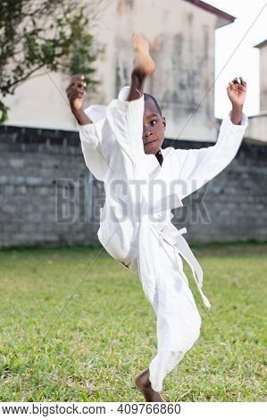Young Child In Kimono Practicing Karate Outdoors