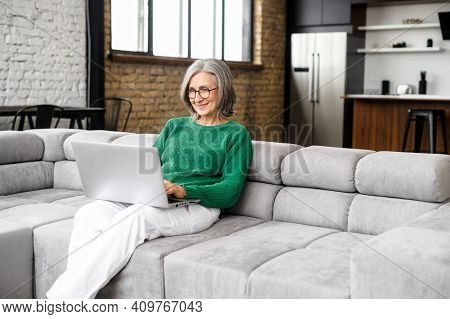 Charming Senior Elderly Woman Spends Leisure Time In Networks On The Computer, Texting Messages, Wat