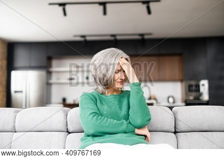Frustrated Senior Woman Feels Headache, Migraine, A Mature Retired Lady Sits On The Couch At Home An