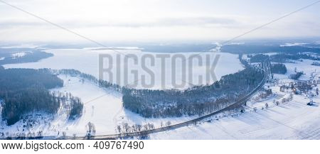 Aerial View Of Winter Landscape, Panorama Of The Frozen Lake In The Middle Of A Forest. Winter Wonde