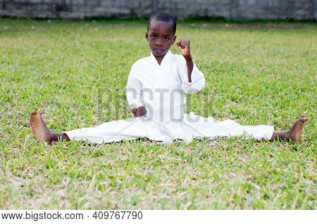 Little Boy Fighting In Karate Outfit Sitting And Showing Martial Art Gesture In The Park