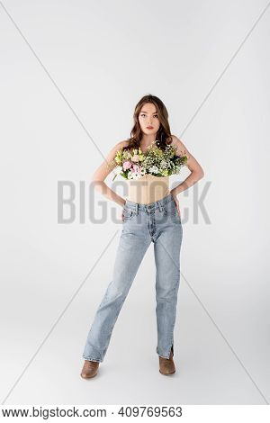 Stylish Model With Flowers In Blouse And Hands On Hips On Grey Background.