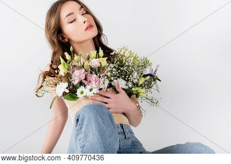 Woman With Closed Eyes Holding Flowers In Blouse Isolated On Grey.