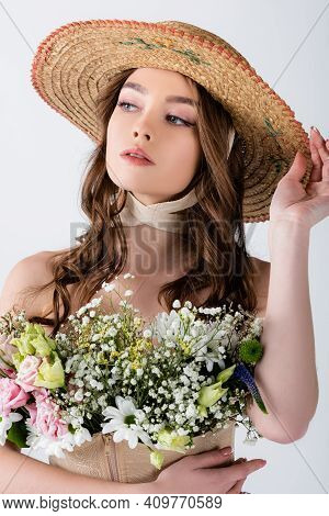 Young Model In Straw Hat And Different Flowers In Blouse Isolated On Grey.