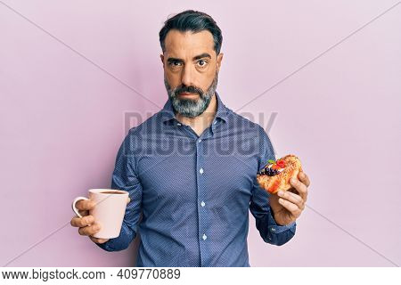 Middle age man with beard and grey hair drinking coffee and eating a pastry skeptic and nervous, frowning upset because of problem. negative person.