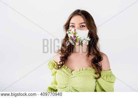 Brunette Woman In Medical Mask With Flowers And Green Blouse Looking At Camera Isolated On Grey.