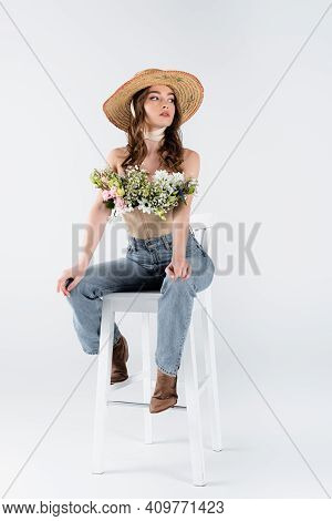 Stylish Model With Flowers In Blouse Posing On Chair On Grey Background.