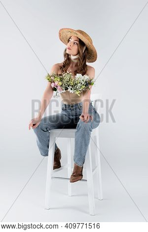 Young Woman In Sun Hat And Flowers In Blouse Looking Away On Chair On Grey Background.