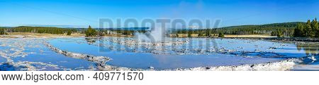 Panorama Of Circular Tiered Thermal Pools Reflecting The Clear Blue Sky With A Steaming Center Build